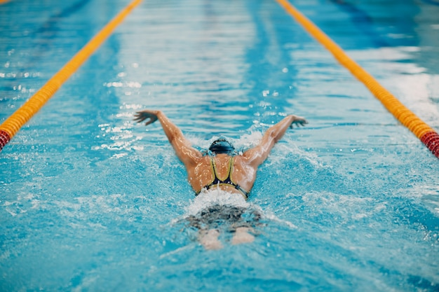 De jonge vrouwenzwemmer zwemt in zwembad