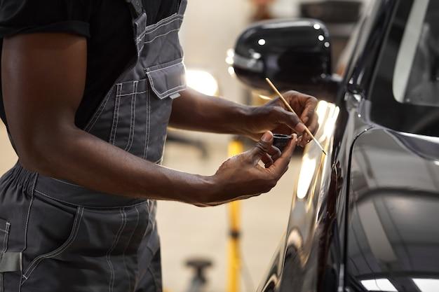 De jonge werknemer van de afro autodienst schildert autodetails
