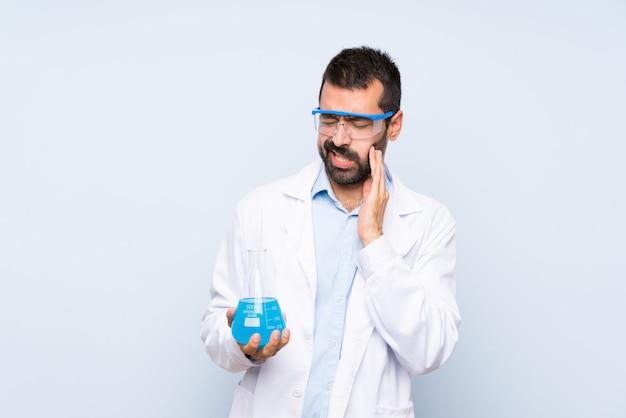 De jonge wetenschappelijke fles van het holdingslaboratorium over geïsoleerde achtergrond met tandpijn