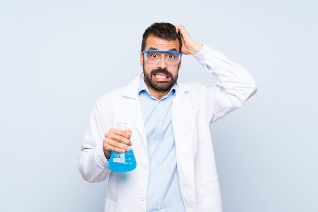 De jonge wetenschappelijke fles van het holdingslaboratorium over geïsoleerde gefrustreerde muur en neemt handen op hoofd