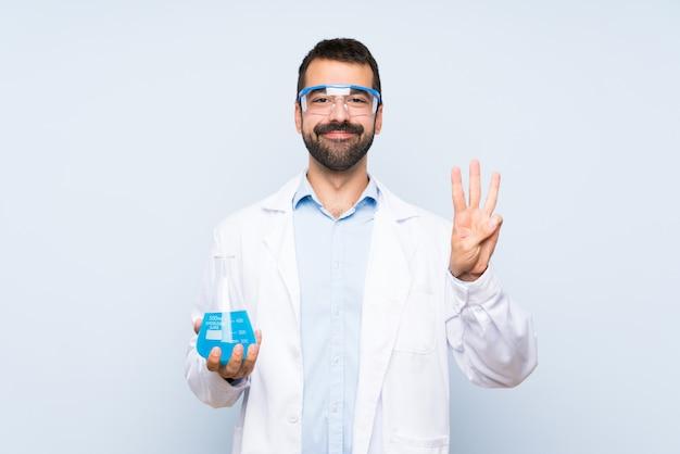 De jonge wetenschappelijke fles van het holdingslaboratorium over geïsoleerde muur gelukkig en tellend drie met vingers