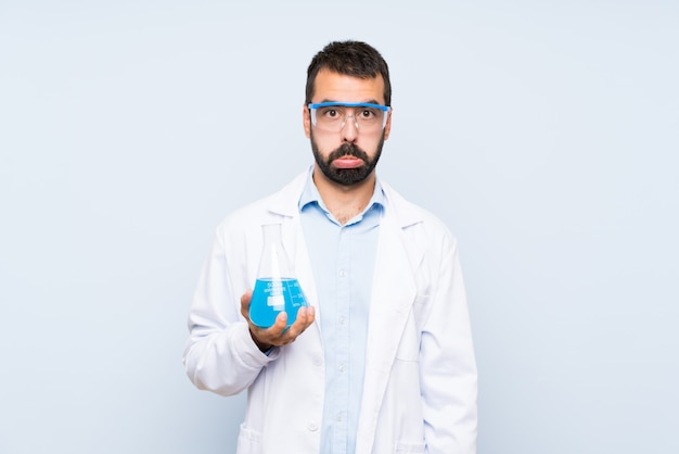 De jonge wetenschappelijke fles van het holdingslaboratorium over geïsoleerde muur met droevige en depressieve uitdrukking