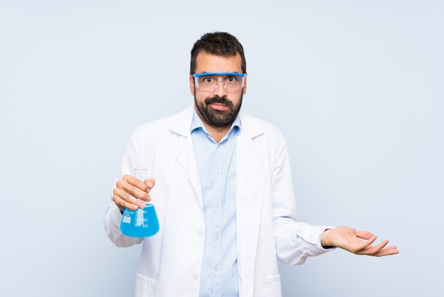 De jonge wetenschappelijke fles van het holdingslaboratorium over geïsoleerde muur ongelukkig voor begrijpt iets niet