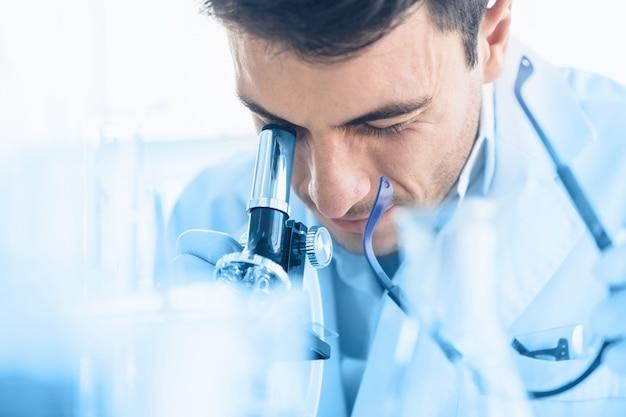 De jonge wetenschapper kijkt door microscoop terwijl het doen van onderzoek naar wetenschappelijk laboratorium