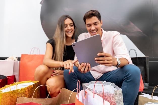 De jonge winkelende tablet van de paarholding