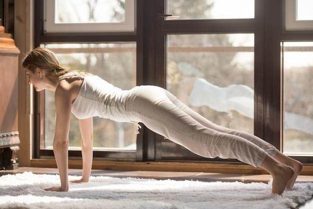De jonge yogi aantrekkelijke vrouw in plank stelt, huisbinnenland