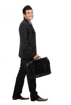 De jonge zakenman loopt en glimlacht