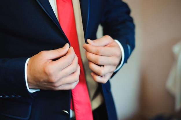 De jonge zakenman trekt een kostuum aan alvorens partners te ontmoeten.