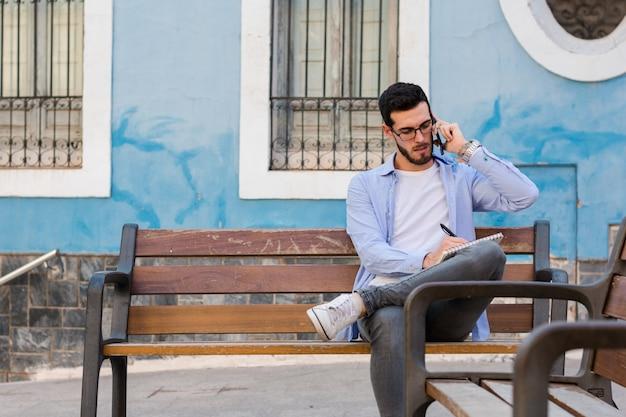 De jonge zakenman zit op een bank terwijl hij op mobiel spreekt en in zijn notitieboekje schrijft
