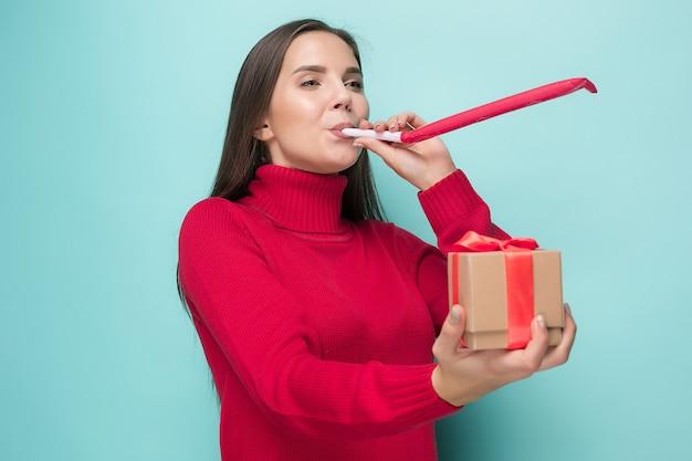 De jonge zakenvrouw met cadeau viert verjaardag, geïsoleerd op blauwe muur