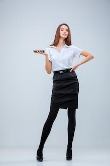De jonge zakenvrouw op grijze muur