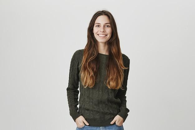 De jonge zekere aantrekkelijke vrouwelijke het glimlachen camera, houdt handen in zakken