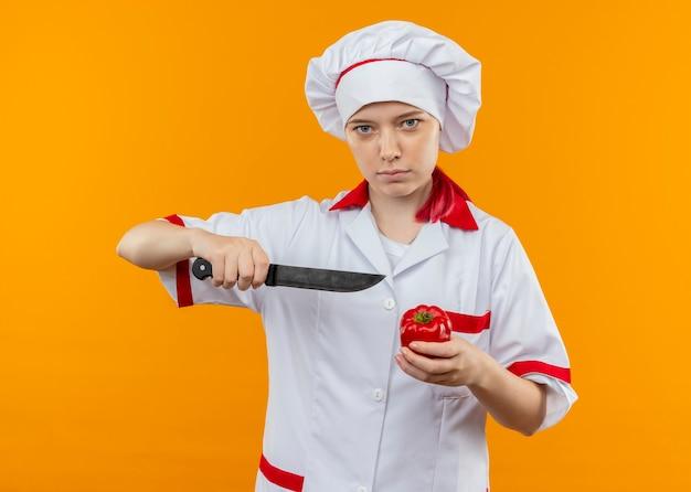 De jonge zekere blonde vrouwelijke chef-kok in eenvormige chef-kok houdt mes en spaanse peper die op oranje muur wordt geïsoleerd