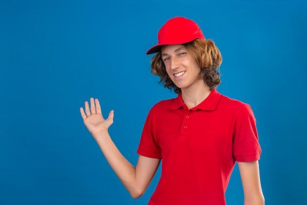 De jonge zekere leveringsmens in het rode eenvormige vriendschappelijke glimlachen die iets voorstellen met overhandigt geïsoleerde blauwe muur