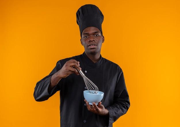 De jonge zelfverzekerde afro-amerikaanse kok in eenvormige chef-kok houdt klop en kom op sinaasappel met exemplaarruimte