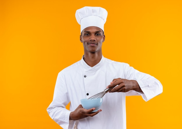 De jonge zelfverzekerde afro-amerikaanse kok in eenvormige chef-kok houdt kom en zwaait geïsoleerd op een oranje achtergrond met kopie ruimte