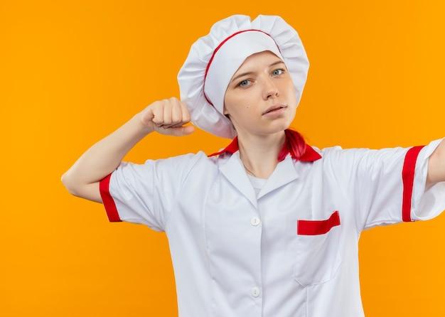 De jonge zelfverzekerde blonde vrouwelijke chef-kok in eenvormige chef-kok beweert te slaan geïsoleerd op oranje muur Gratis Foto