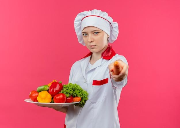 De jonge zelfverzekerde blonde vrouwelijke chef-kok in eenvormige chef-kok houdt groenten op plaat en houdt wortel uit geïsoleerd op roze muur