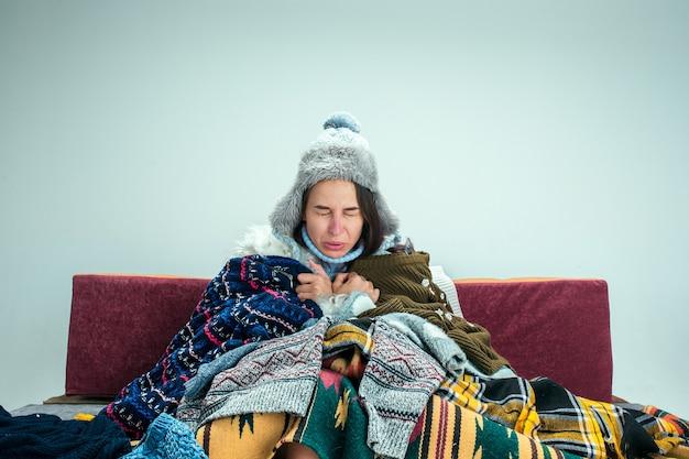 De jonge zieke vrouw met rookkanaal zittend op de bank thuis of studio bedekt met warme gebreide kleding. ziekte, griep, pijn concept. ontspanning thuis. gezondheidszorgconcepten.