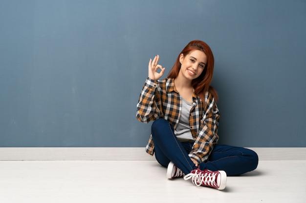 De jonge zitting van de roodharigevrouw op vloer die ok teken met vingers toont