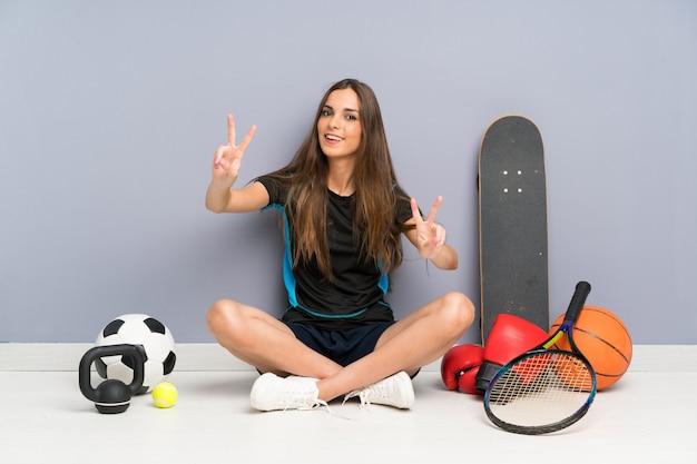 De jonge zitting van de sportvrouw op de vloer die en overwinningsteken glimlacht toont