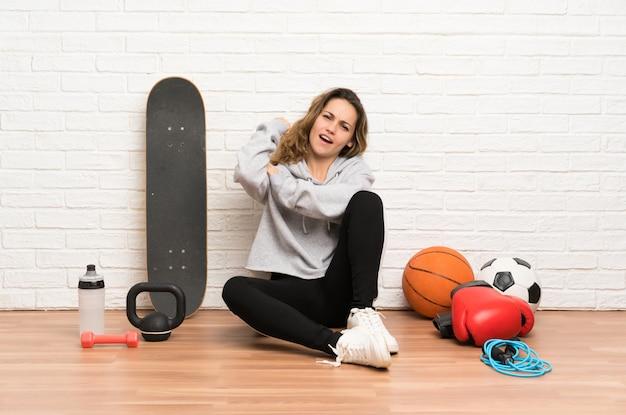De jonge zitting van de sportvrouw op de vloer die sterk gebaar maken