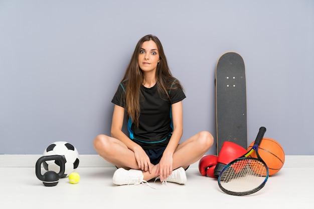 De jonge zitting van de sportvrouw op de vloer die twijfels hebben en met verwarren gezichtsuitdrukking