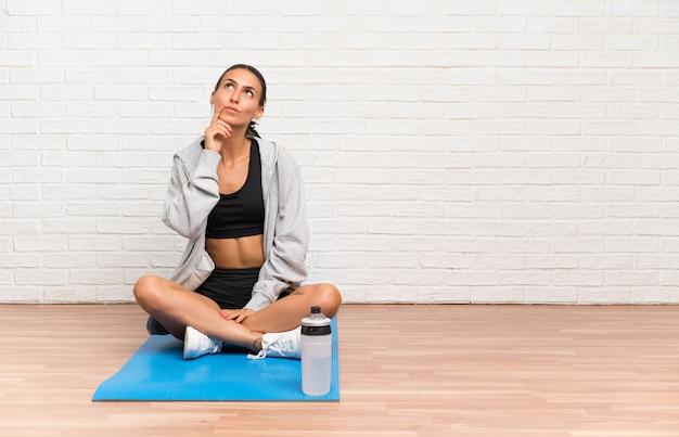 De jonge zitting van de sportvrouw op de vloer met mat die een idee denkt