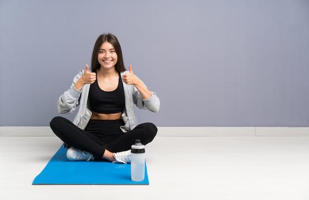 De jonge zitting van de sportvrouw op de vloer met mat geven duimen op gebaar