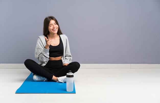 De jonge zitting van de sportvrouw op de vloer met mat richt vinger op u