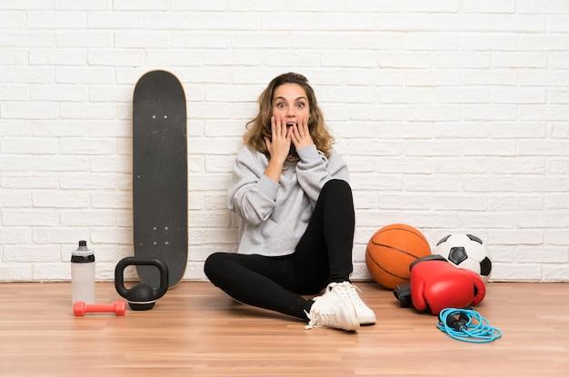 De jonge zitting van de sportvrouw op de vloer met verrassingsgelaatsuitdrukking