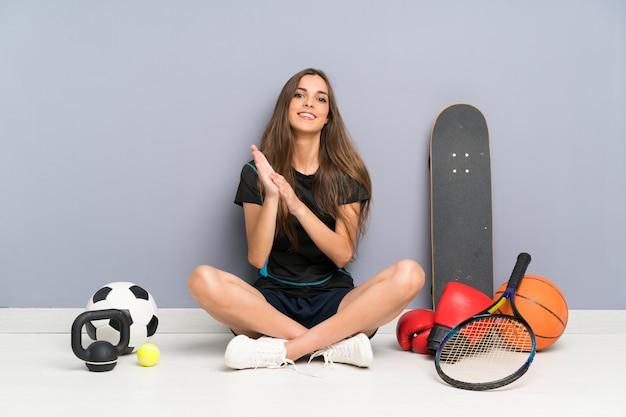 De jonge zitting van de sportvrouw op vloer het toejuichen