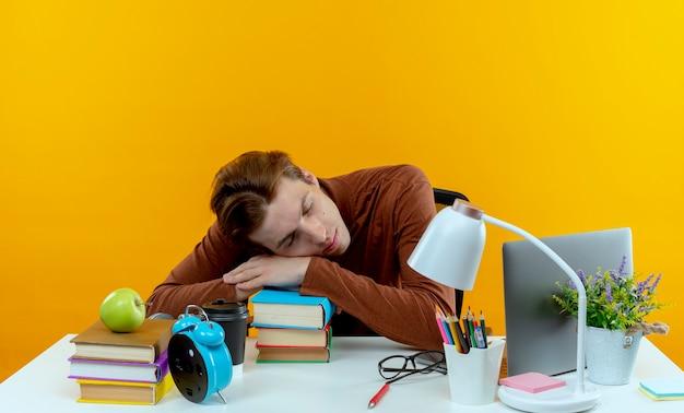 De jonge zitting van de studentenjongen aan bureau met schoolhulpmiddelen die hand op boeken zetten en slaap die op gele muur wordt geïsoleerd