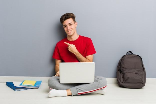 De jonge zitting van de studentenmens die op zijn huisvloer laptop houdt