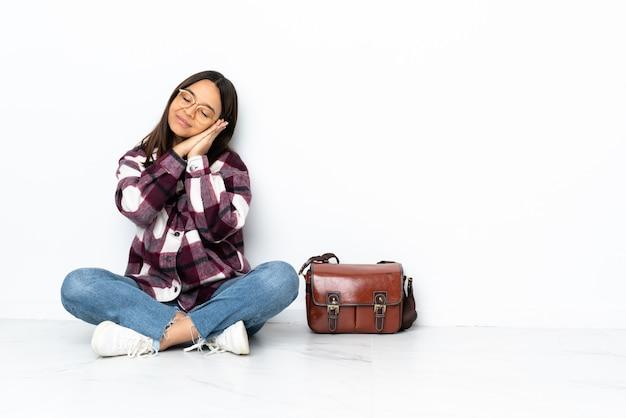 De jonge zitting van de studentenvrouw op de vloer die slaapgebaar in dorable uitdrukking maakt