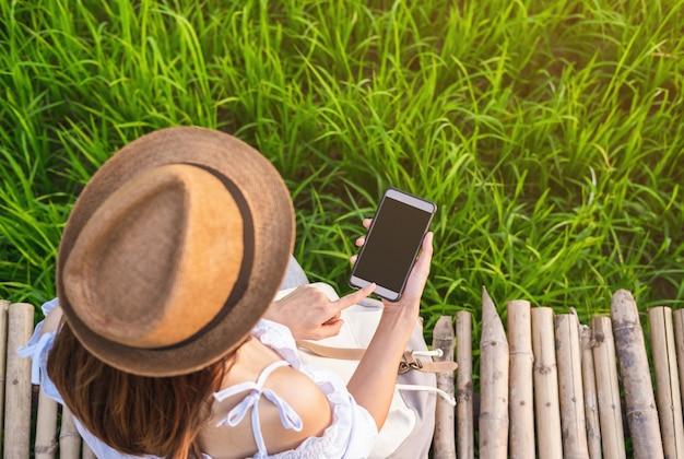De jonge zitting van de vrouwenreiziger op bamboeweg en het gebruiken van slimme telefoon bij groen padiegebied
