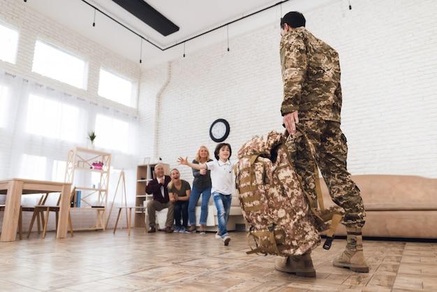 De jonge zoon ontmoet thuis een man in camouflage.