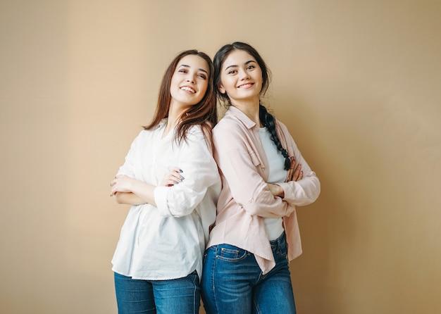 De jonge zorgeloze donkerbruine glimlachende zusters van meisjesvrienden in toevallige overhemden en jeans die op beige achtergrond worden geïsoleerd