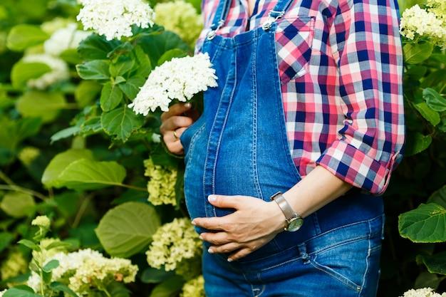 De jonge zwangere vrouw in denimoverall houdt bloemen