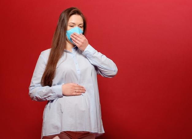 De jonge zwangere vrouw op rode muur in beschermend medisch masker houdt op maag en niest
