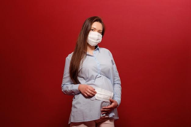 De jonge zwangere vrouw op rode muur in beschermend medisch masker houdt op maag