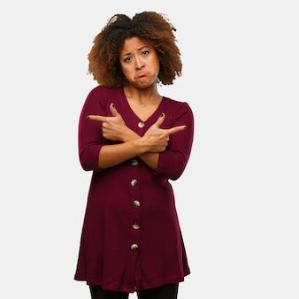 De jonge zwarte afrovrouw beslist tussen twee opties