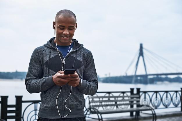 De jonge zwarte atleet luistert naar muziek na een training in de stad