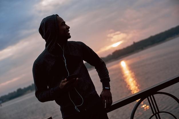 De jonge zwarte atleet met kap luistert naar muziek en kijkt naar de zonsopgang