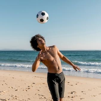 De jonge zwarte bal van het atleten speelvoetbal op strand