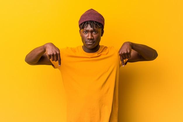 De jonge zwarte mens die rastas over gele muur draagt wijst neer met vingers, positief gevoel.