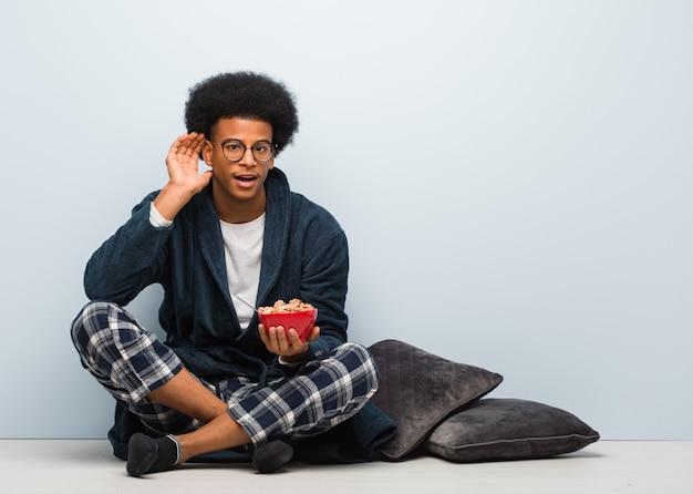 De jonge zwarte mensenzitting en het hebben van een ontbijt proberen om een roddel te luisteren