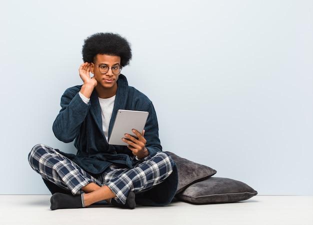 De jonge zwarte mensenzitting op zijn huis en holding zijn tablet probeert aan het luisteren van een roddel