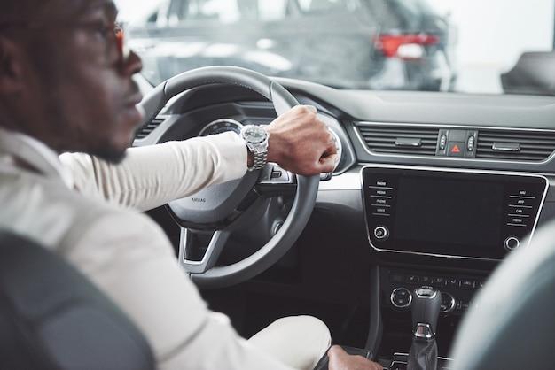 De jonge zwarte nieuwe auto van de zakenmantestaandrijving. rijke afro-amerikaanse man