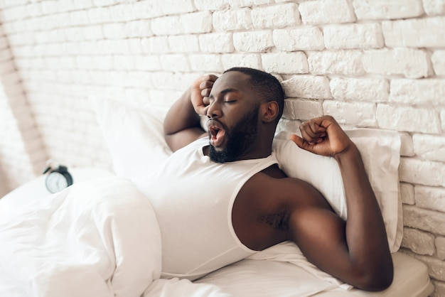 De jonge zwarte, ontwaakte man ligt languit in bed.